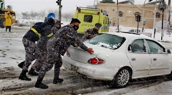 عناصر من الدفاع المدني الأردني يساعدون مواطنين عالقين بسبب الثلوج (تويتر)