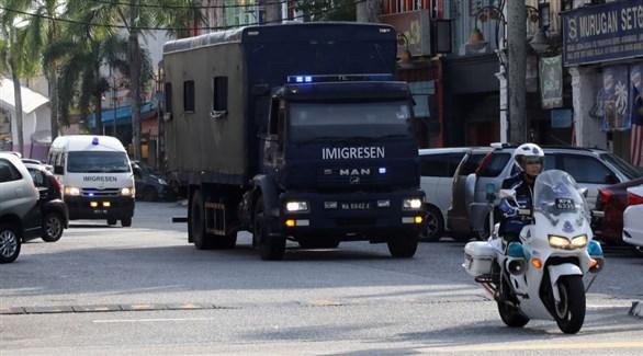 شرطي مرور ماليزي يتقدم شاحنة تقل مهاجرين لترحيلهم إلى ميانمار (تويتر)