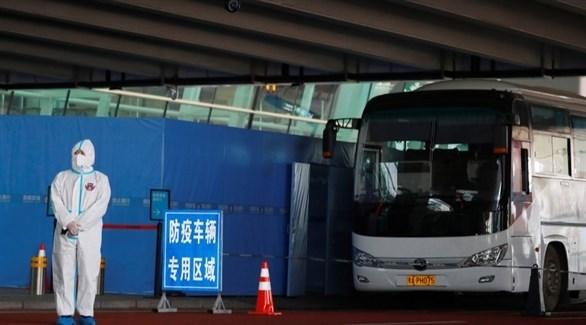 صيني أمام حافلة فريق خبراء منظمة الصحة العالمية في ووهان (أرشيف)
