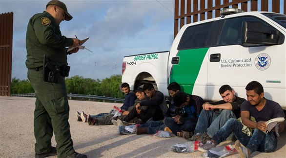 عنصر من حرس الحدود الأمريكي مع مهاجرين غير شرعيين (أرشيف)