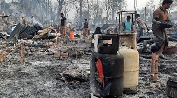 لاجئون من الروهينجا يعاينون آثار الحريق في المخيم (تويتر)