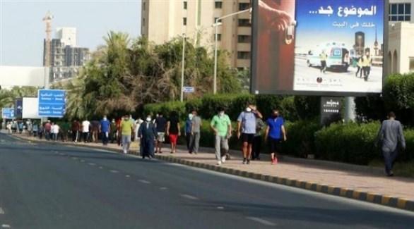 مواطنون ومقيمون يمارسون رياضة المشي في أحد أحياء الكويت العاصمة  (أرشيف)