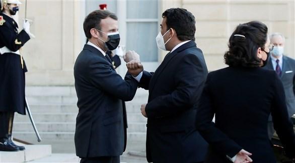 ماكرون والمنفي يتبادلان التحية في العاصمة باريس (أ ف ب)