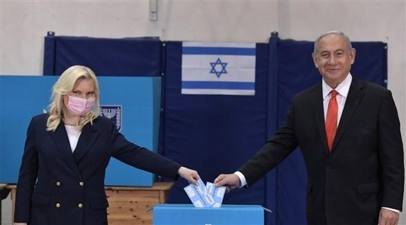 رئيس الوزراء الإسرائيلي بنيامين نتانياهو خلال الإدلاء بصوته رفقة زوجته (تويتر)