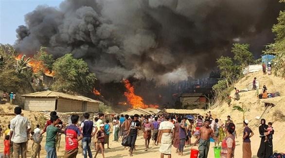 لاجئون روهينجا يشاهدون الحريق الذي دمر مخيمهم (أرشيف)