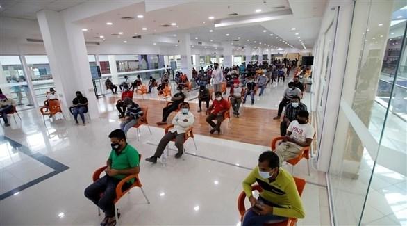أشخاص ينتظرون دورهم للحصول على لقاح ضد كورونا في البحرين (رويترز)