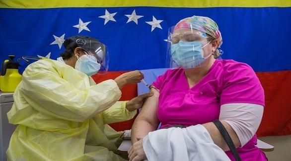 ممرضة فنزويلية تطعم سيدة ضد كورونا في كاراكاس (أرشيف)