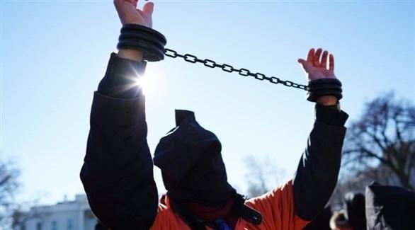 شخص يرتدي الأصفاد وملابس السجن البرتقالية (تعبيرية)
