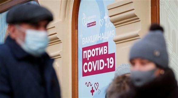 روسيان أمام مركز لتوزيع لقاحات مضادة لكورونا (رويترز)