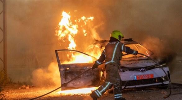 عنصر من الدفاع المدني الإسرائيلي يحاول إخماد حريق في سيارة بعد مواجهات في اللد (تويتر)