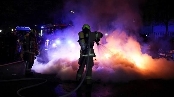 فرق إطفاء تخمد نيراناً أشعلها المتظاهرون في برلين (رويترز)