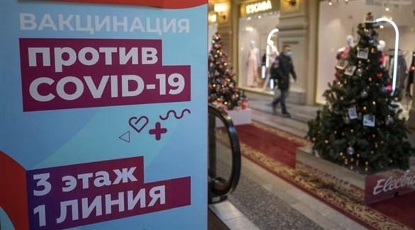 لوحة إرشادية بجوار مركز لتقديم اللقاحات المضادة لكورونا في روسيا (رويترز)