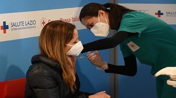 متطوعة في الصليب الأحمر الإيطالي تُطعم سيدة ضد كورونا في مقاطعة لازيو (أرشيف)