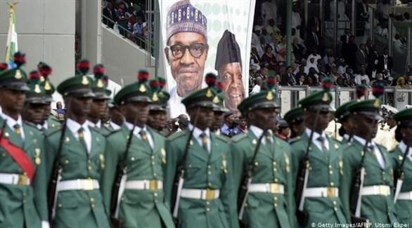عناصر من الجيش النيجيري خلفهم صورة للرئيس محمد بخاري (أرشيف)