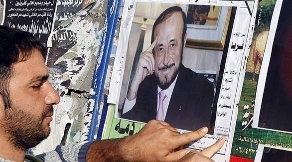 شخص يعلق صورة رفعت الأسد (أرشيف)