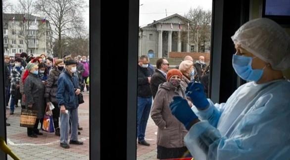روس أمام مركز  تطعيم كورونا (أرشيف
