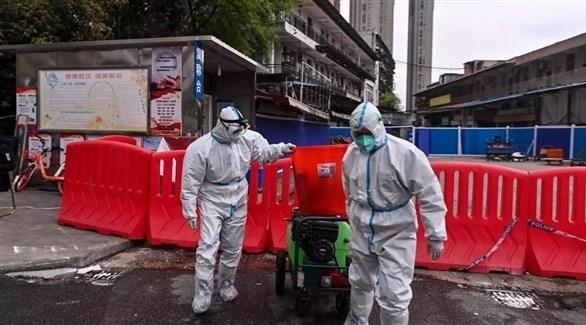 عمال يرتدون بدلات واقية في ووهان الصينية مهد فيروس كورونا (أرشيف)