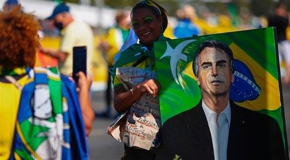 امرأة تحمل صورة للرئيس البرازيلي جايير بولسونارو (أرشيف / غيتي)