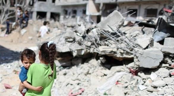 طفلان أمام منزل مدمر خلال الحرب الأخيرة في غزة (أرشيف)