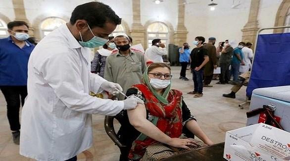 ممرض يُطعم باكستانية ضد كورونا في مركز تلقيح بكراتشي (أرشيف)