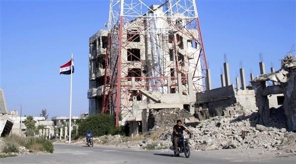 مدنيان في أحد شوارع درعا وسط الآنقاض (أ ف ب)