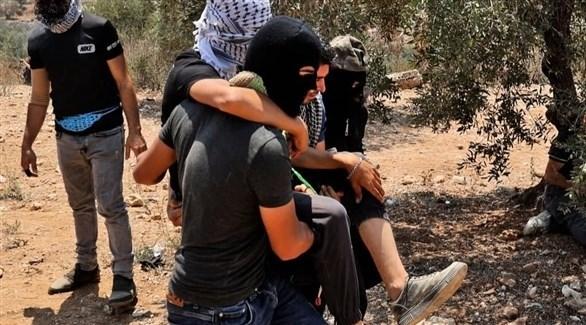 فلسطينيون يجلون مصاباً في المواجهات مع الجيش الإسرائيلي (تويتر)