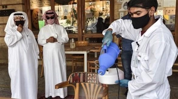 نادل يعقم طاولة قبل جلوس ضيفين سعوديين عليها (أرشيف)