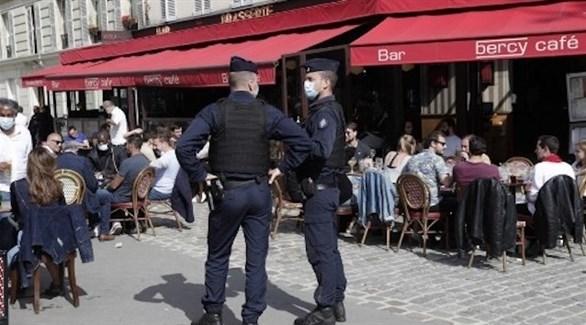 رجلا شرطة فرنسيان يراقبان التزام زوار إحدى المطاعم بالاجراءات الاحترازية (أرشيف)
