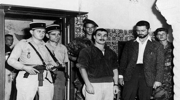 ياسف سعدي وسط ضباط من الشرطة والجيش الفرنسيين بعد اعتقاله في 1957 (أرشيف)